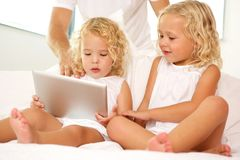 Little girls sitting on bed with digital tablet Stock Photos