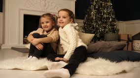 Little girls sitting on carpet looking at photographer. Christmas holiday concept. stock photos