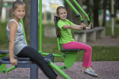 Little girls sitting on exercise equipment Royalty Free Stock Photos