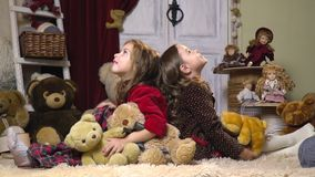 Girls sit with their backs to each other and are surprised to a lot of plush toys, slow motion stock video