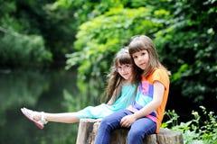 Little girls sitting on stump Stock Photos