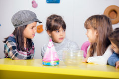 Little girls sitting and talking in the playroom Stock Image