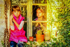 Little girls sitting by the window Royalty Free Stock Images