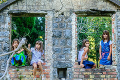 Little girls sitting on the window opening. Four little girls playing around old house ruins Royalty Free Stock Image