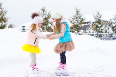 Little girls skating on ice rink outdoors in Royalty Free Stock Photos
