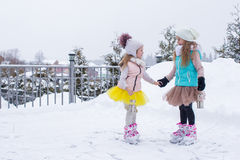 Little girls skating on ice rink outdoors in Stock Image