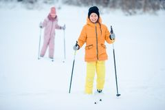 Child skiing in the mountains. Winter sport for kids. Little girls skiing in the mountains together. Winter sport for kids royalty free stock photos