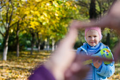 Little girls smiling face in a finger frame Stock Photo