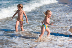 Little girls in the spray of waves at sea Stock Images