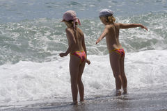 Little girls stand at the sea during a storm Royalty Free Stock Images