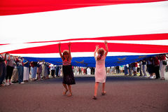 Little girls stand underneath US Flag Royalty Free Stock Images