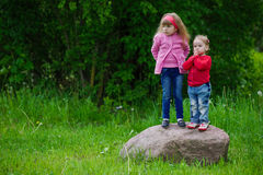 Little girls standing on big stone. Photo of cute little girls standing on big stone Stock Image