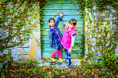Little girls standing in front of the doors. Little girls standing in front of the green doors stock images