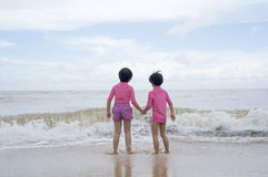 Little girls standing in front of the sea wave Royalty Free Stock Photo