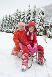 Little girls staying on the sledge Stock Photos