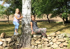 Little girls on stone wall Royalty Free Stock Photography
