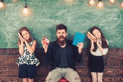 Little girls students tired of study in school. Monster teacher shout at sleepy pupils. Angry man with alarm clock and. Little girls students tired of study in stock photo