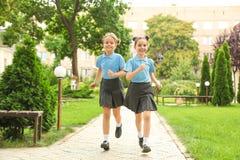 Little girls in stylish school uniform. Outdoors stock photos