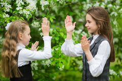 Little girls in stylish school uniforms play outdoors in the blossoming apple park stock image
