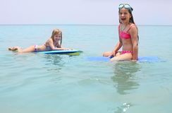 Little girls with surfing boards playing on tropical ocean beach. Summer water fun for surfer kids royalty free stock image