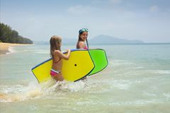 Little girls with surfing boards playing on tropical ocean beach. Summer water fun for surfer kids stock photo