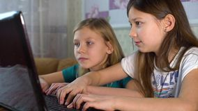 Little girls surfing internet together on laptop. Friends sitting in front of monitor and pushing keyboard buttons. home education, online surfing and school stock video