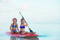 Little girls swimming on surfboard during summer Royalty Free Stock Images