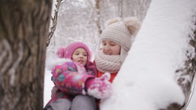 Little girls swinging on the branches of trees, snow-covered stock video