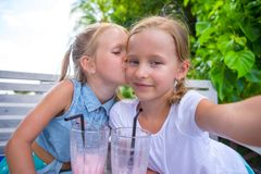 Little girls taking selfie and drinking tasty Stock Images
