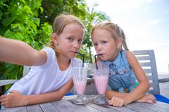 Little girls taking selfie and drinking tasty Royalty Free Stock Image