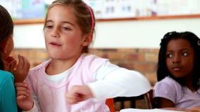Little girls telling secrets in the classroom. In elementary school stock video footage