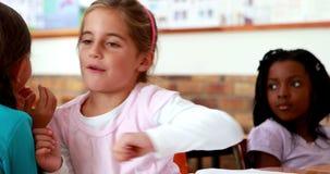 Little girls telling secrets in the classroom. In elementary school stock footage