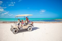 Little girls and their mother driving golf cart at Stock Images