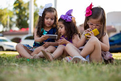 Little girls with their own phones. Potrait of three cute little girls each one using their own smart phone at a park Stock Photography