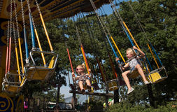 Little girls thrilled on carousel swing ride. Two young girls ride the carousel swings ride at Como Park Zoo in St. Paul, Minnesota. Como Park Zoo was founded in royalty free stock photo