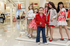 Little girls trying on clothes together with mannequins Royalty Free Stock Photo