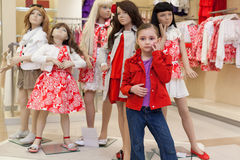 Little girls trying on clothes together with mannequins royalty free stock image