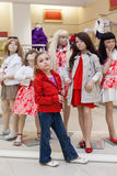 Little girls trying on red clothes together with mannequins Royalty Free Stock Photos