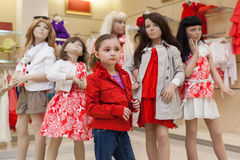 Little girls trying on red clothes together with mannequins Royalty Free Stock Images