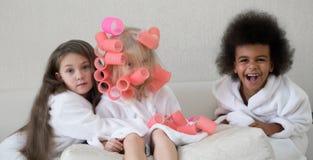Little girls twirl hair curlers. stock photos