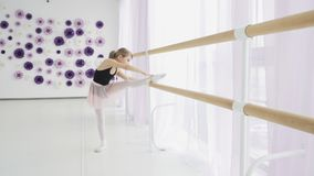 Little girls using ballet barre when doing leg stretching exercises in dance studio stock footage