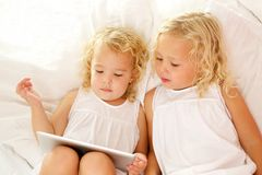 Little girls using digital tablet on bed. Top view portrait of little girls using digital tablet on bed royalty free stock images