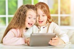 Little girls using tablet. Two cute little girls using digital tablet Stock Photos
