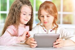 Little girls using tablet. Two cute little girls using digital tablet Royalty Free Stock Photos