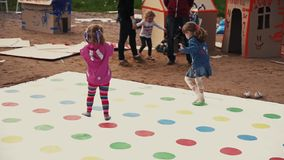 Little girls walk on field of twister game. Summer festival. Painted faces stock footage
