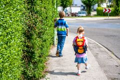Little girls walking away with her filled backpack.  Stock Photography