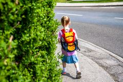 Little girls walking away with her filled backpack.  Royalty Free Stock Photography