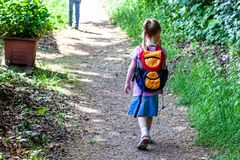 Little girls walking away with her filled backpack.  Royalty Free Stock Image