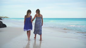 Little girls walking by the sea on the white beach. Kids on beach vacation in the evening. Little girls having fun at tropical beach during summer vacation stock video footage