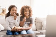 Little girls watching cartoon and eating popcorn at home. Little girls watching cartoon and eating popcorn, sitting on sofa at home stock images